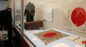 兵士の無事を願った出征旗や軍服など、戦争に関する資料が展示された会場=松本市立博物館で