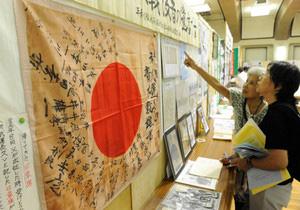 戦地から家族の元へ戻ってきた日章旗などが並ぶ会場=名古屋市昭和区の市公会堂で