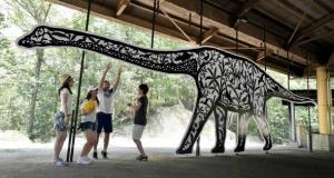 夏の展示「太古の森」。キャンプ場に等身大の恐竜をかたどった作品が並ぶ=竜王町の希望が丘文化公園で