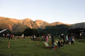 北尾根高原でオレンジ色に染まる白馬の山々をバックに日の出を待つ人たち