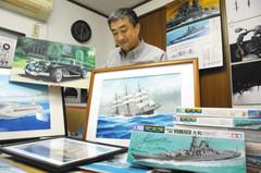 上田毅八郎さんが描いた艦船や車の絵を並べる星野順啓さん=浜松市中区で