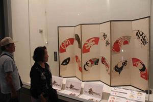 12ある山組の招き扇が描かれたびょうぶ。展示を通し、各図柄の由来を解説している=長浜市曳山博物館で