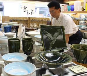 多彩な美濃焼が並ぶ会場を運営する小林さん=岐阜市美殿町の小林漆陶で