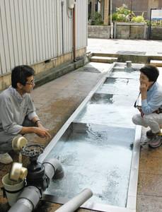 豊富なわき水が出る清水庵の清水で談笑する加藤久仁夫さん(左)ら