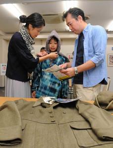 昭和館巡回特別企画展で、防空頭巾など戦時中の衣服を試着する親子=名古屋市中区の桜華会館で
