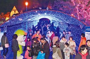 青一色の光のアーチ内を歩く大勢の来場者=敦賀市の金ケ崎緑地で