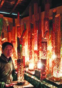 竹と電球で銀河を表現した光のオブジェを紹介する三代沢さん=伊賀市蓮池で