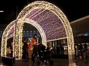 イルミネーションゲートをくぐって楽しむ親子連れたち=富山駅南口の駅前広場で