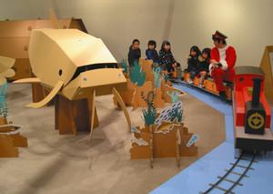 電動の段ボール製の機関車に乗って遊ぶ子どもたち=守山市水保町の佐川美術館で