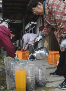 ペットボトルの灯明に水を入れる参加者たち=喬木村の法運寺で