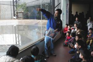 一般公開されているトキ(左奥)を見ながら飼育員(中)の解説を聞く来場者=能美市のいしかわ動物園で