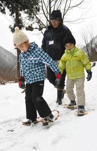 かんじきを装着して雪上を歩く子どもら=白山市尾添で