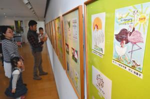 今年のえと「酉」を題材に描かれた絵本作家らによる年賀状作品=射水市大島絵本館で