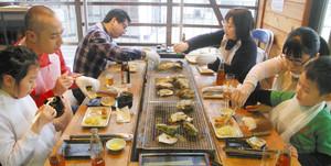 こんろで焼いたカキなどを味わう来場者=石川県穴水町ののと鉄道穴水駅で