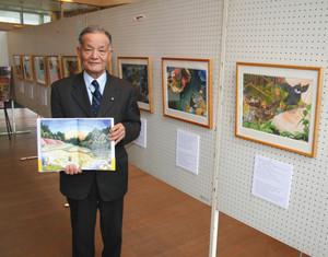 ケロン村を舞台にした絵本の原画展を開いている上乗秀雄さん=能登町のコンセールのとで