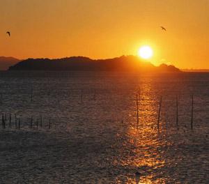 島陰から太陽が昇る寝釈迦の光景=蒲郡市形原町で