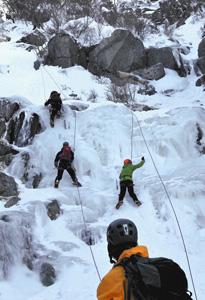 氷に覆われた岩壁を登る登山者=菰野町の御在所岳で