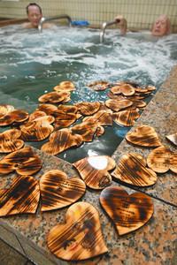 ハート形のヒノキが浮かぶ風呂で疲れを癒やす利用客ら=射水市鏡宮の天然温泉海王で