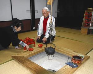 食事をするいろりのある部屋で、輪島塗のわんを並べる西山茂男さん(右)、繁子さん夫妻=輪島市三井町新保で