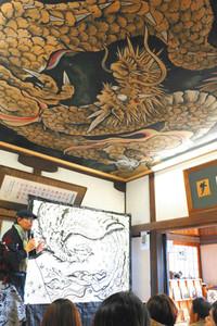 大天井画(上方)の完成記念に「鳳凰」を早描きする斎灯サトルさん(左)=掛川市の永福寺で