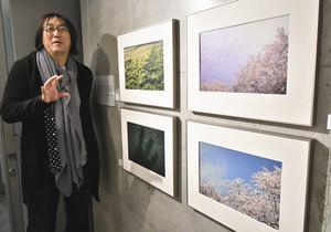 東日本大震災の発生前と後に、同じ場所から撮影した風景写真を並べた作品を説明する高崎勉さん=高岡市ミュゼふくおかカメラ館で