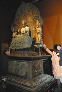 釈迦三尊像の複製を触る参加者=高岡市末広町で
