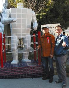 タイルマンの像の完成を祝う嶋田さん(左)と鈴木さん=JR多治見駅前で