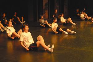 演劇の基礎トレーニングをする中高生と外国人の俳優ら=県利賀芸術公園で