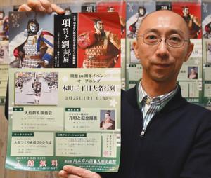 項羽と劉邦展など10周年イベントのチラシを掲げる木田事務局長=飯田市川本喜八郎人形美術館で
