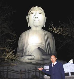 ライトアップが始まった布袋の大仏を紹介する前田さん=江南市木賀町で