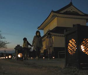 明かりがともされた鋳物灯籠=桑名市の七里の渡し跡で