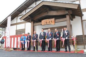 テープカットし、天龍峡温泉交流館のオープンを祝う関係者たち=飯田市で