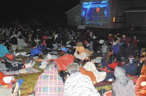 山の上で宇宙への旅をテーマとした映像を見る参加者たち=阿智村で