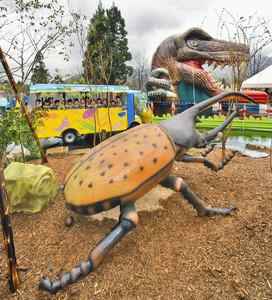 巨大な昆虫ロボット(手前)が置かれたコースを電気自動車で巡る園児たち=勝山市の長尾山総合公園で
