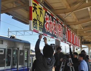 おかえり祭りをPRする看板を取り付ける部員たち=JR美川駅で
