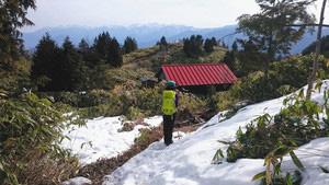 山頂近くにある残雪の避難小屋からは中央アルプスの峰が望めた