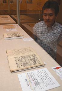 バラが登場する文献が並ぶ企画展=明和町竹川の斎宮歴史博物館で
