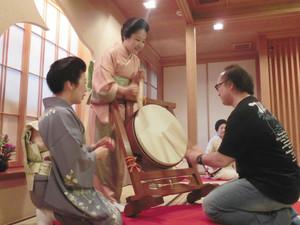 芸妓とお座敷遊びを楽しむ参加者(右)=2016年9月、金沢市主計町で