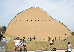 独特の形のミュージアムの前で写真を撮る家族連れ