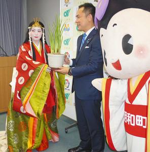 明和町の花のハナショウブを贈って斎王まつりをPRする中前さん(左)=県庁で