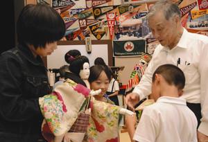 阿部団長(右)に人形の操り方を教わる子どもたち=長浜市富田町で