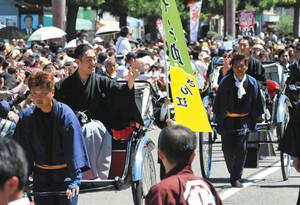 豊国神社の参道をお練りし、沿道を埋めた人たちに手を振る勘九郎さん(手前)と七之助さん=名古屋市中村区で