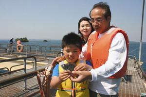 お父さんとお母さんとともに思い出に残るクロダイを手にする遠藤雅和君