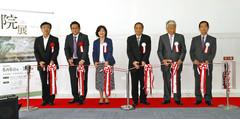開幕を記念してテープカットを行う関係者ら。左から4人目が小山硬さん=浜松市中区のクリエート浜松で