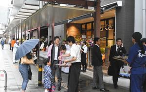 開業を迎え、店舗前で通行人に試食品を配るスタッフら=大津市のJR大津京駅前で