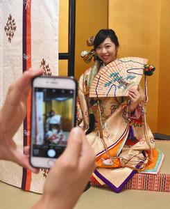 模擬十二単を着て撮影を体験する西村さん=大津市神宮町の近江神宮衣裳部で
