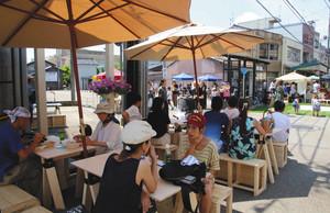 手作りのベンチやテーブルで食事を楽しむ人たち=氷見市中央町で