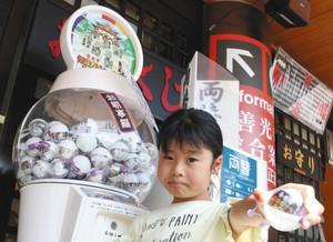 おみくじと模型が入った「ガチャみくじ」を楽しむ参拝客の子ども=長野市元善町の善光寺で