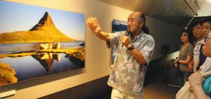 撮影の裏話と共に写真への思いを語る高砂淳二さん(左)=高岡市福岡町福岡新で