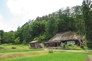 山に寄り添うようにひっそりと立つかやぶき屋根の民家